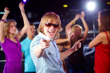 Portrait of energetic dancer on background of happy friends having fun photo
