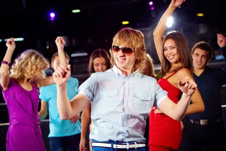Portrait of stylish guy dancing on background of energetic friends photo