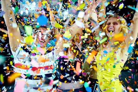 Photo of excited teenagers in confetti raising their arms expressing joy