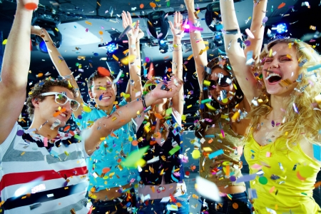 Photo of excited teenagers in confetti raising their arms expressing joy  Stock Photo - 6770088