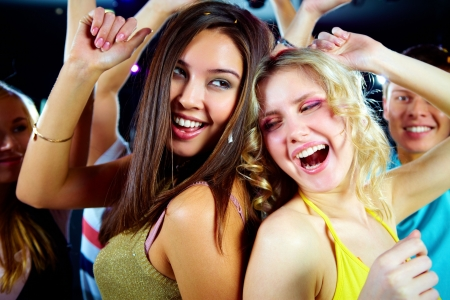 Two joyful girls dancing in night club and having fun photo