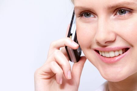Close-up portrait of a cute young pretty woman speaking on the phone with friend photo