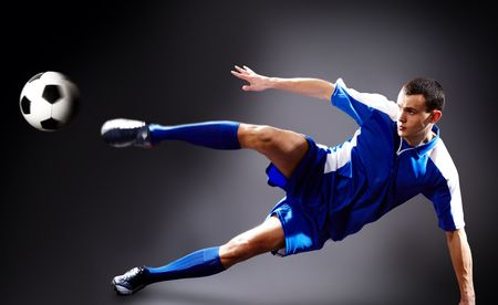 Image of soccer player doing flying kick with ball