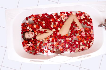 lying in bathtub: Pretty woman enjoys in the bathtub with petals of rose