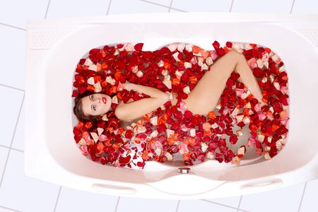 lying in bathtub: Portrait of young woman lying in the bathtub with red petals