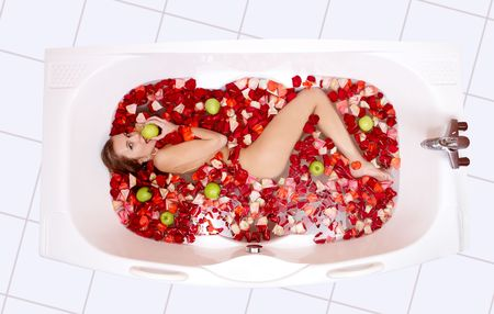 lying in bathtub: Portrait of attractive woman lying in the bathtub and eating apple   Stock Photo