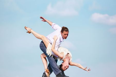 Image of passionate couple dancing over blue sky background photo