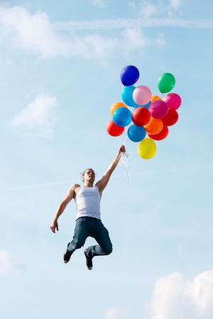 man flying: Image of young man jumping and holding colorful balloons