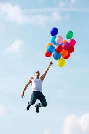 Imagen de hombre joven saltando y la celebración de globos de colores