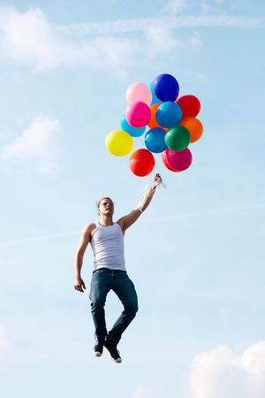 Image of young man with colorful balloons over bright sky background photo