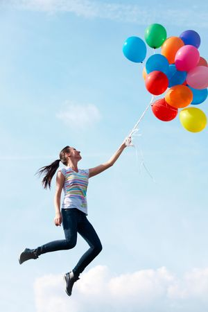 Image of young woman with colorful balloons flying photo