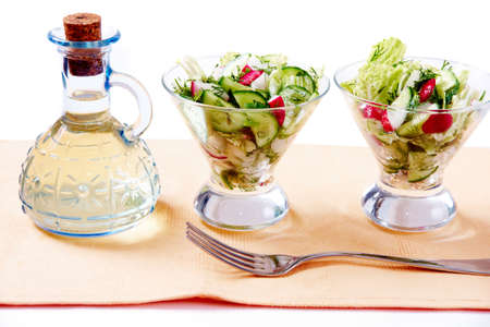 Image of two portions of salad with bottle of oil and fork near by  Stock Photo - 6834138