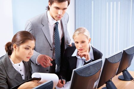 Smart co-workers looking at monitor while confident man explaining something Stock Photo - 6893418