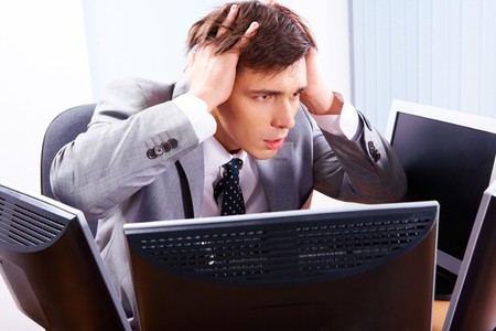 Portrait of frustrated employer surrounded by computers with his hands on head photo