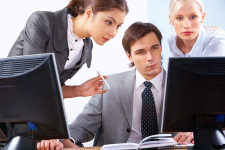 Serious business people looking at computer screen during corporate meeting Stock Photo - 6894054