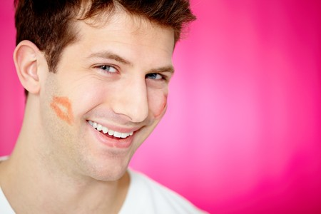 Handsome man with print of lipstick on his cheek smiling at camera photo