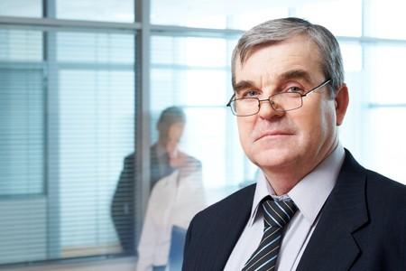serious businessman: Portrait of mature boss in eyeglasses looking at camera