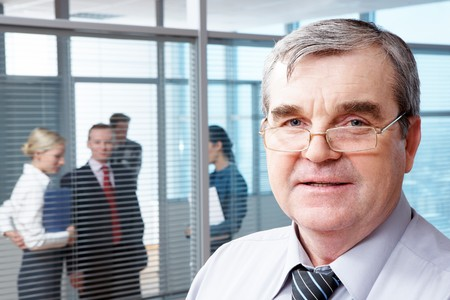 Portrait of mature boss in eyeglasses looking at camera in office Stock Photo - 6893498