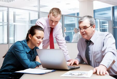 Portrait of serious business partners looking at laptop screen in office Stock Photo - 6893485