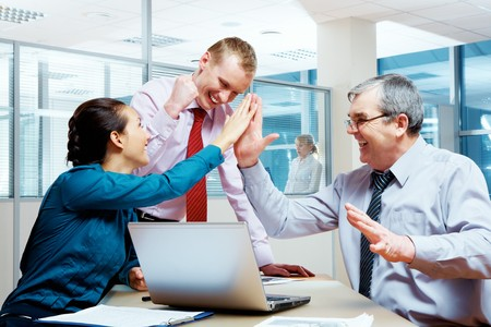 Image of glad businesspeople congratulating each other on corporate victory  photo