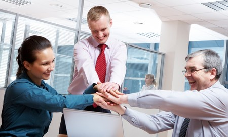 Image of glad businesspeople making pile of hands at meeting  photo