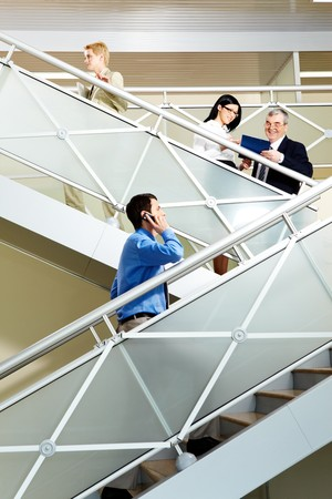 Photo of busy partners communicating while going upstairs in office building photo
