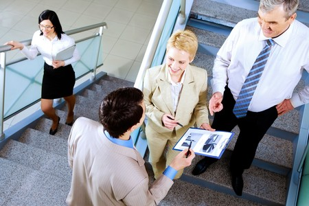 busy partners discussing papers while on stairs of office building photo