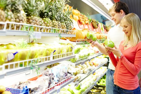 Portrait of healthy couple looking at fruits in supermarket during shopping photo