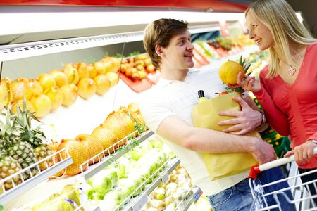 Portrait of happy couple looking at each other in supermarket photo