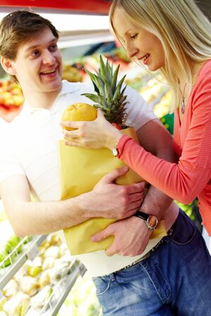 Portrait of female putting large orange into paperbag held by smiling man in supermarket Stock Photo - 6894252