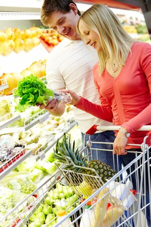 Portrait of happy couple choosing greenery in supermarket photo