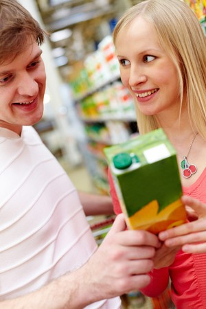 Portrait of female looking at smiling man in supermarket while choosing juice Stock Photo - 6894203