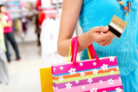 bright center: Close-up of woman holding her credit card and carring paper bag