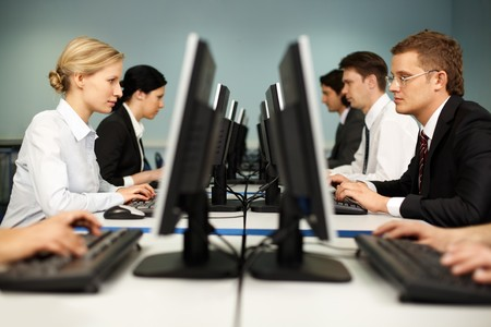 person at computer: Image of smart people sitting at the tables at computer class