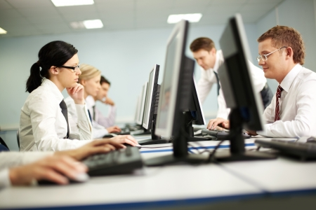 working place: Businesspeople sit at tables and look at their monitors