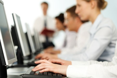 input: Image of female hands typing on keyboard in a working environment