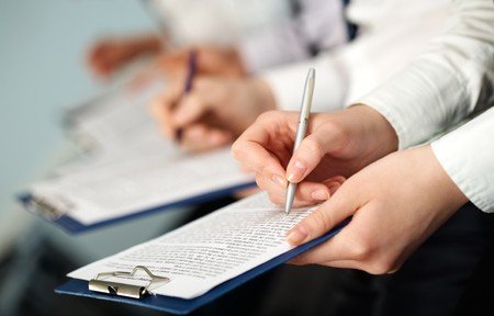 Row of hands of business people holding documents and pens Stock Photo - 6893410