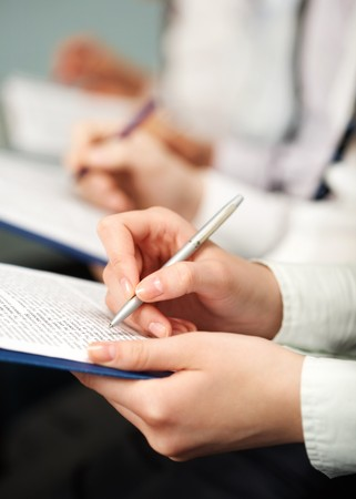 People make notes in documents at seminar Stock Photo - 6893432