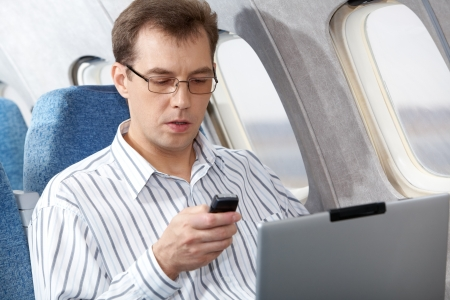 Image of busy businessman working during flight photo
