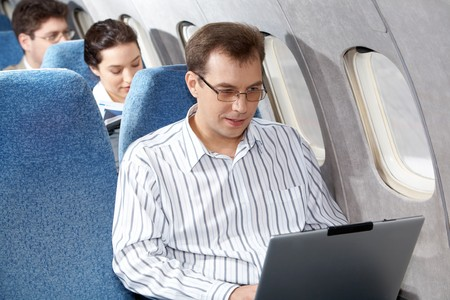 Image of young businessman working with laptop during flight photo
