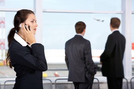 Image of businesswoman calling by phone in the airport  photo