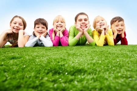 Imagen de feliz de los niños y niñas que acostado en una hierba verde Foto de archivo
