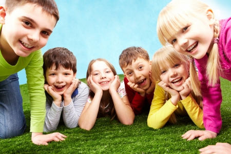 Image of playful children lying on a green grass and looking at camera photo