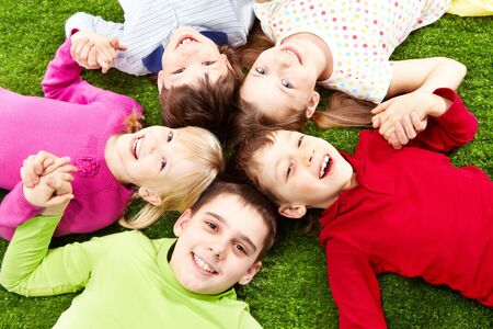 Image of happy friends lying on the grass and smiling  Stock Photo - 6894282