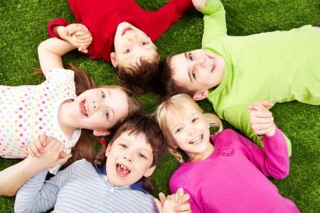 ni�as jugando: Imagen de la sonriente joven de ni�os y ni�as que se juega sobre el c�sped