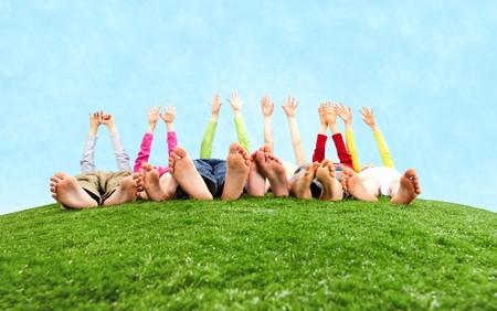 pied jeune fille: Image de plusieurs enfants allong�s sur l'herbe et les �tirements leurs mains vers le soleil