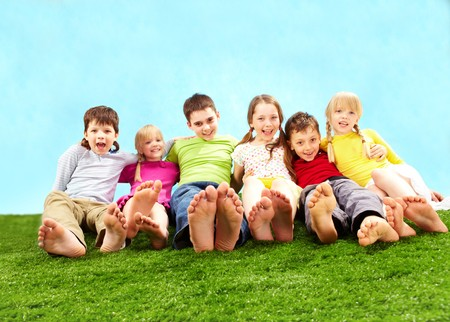 kids feet: Group of happy children relaxing on the grass together Stock Photo