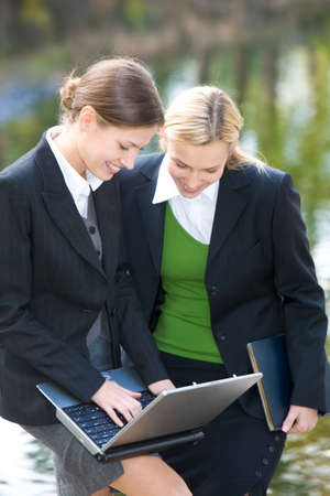 Portrait of businesswomen looking at laptop near lake  Stock Photo - 6893463