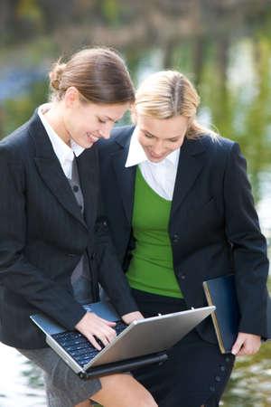 Portrait of businesswomen looking at laptop near lake  photo