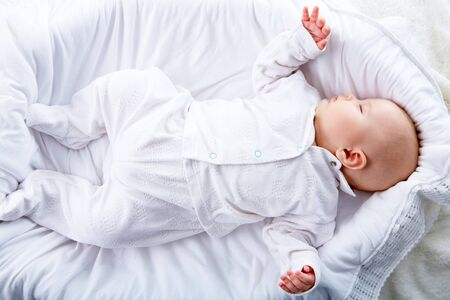 Above view of baby lying in comfortable cradle at home photo